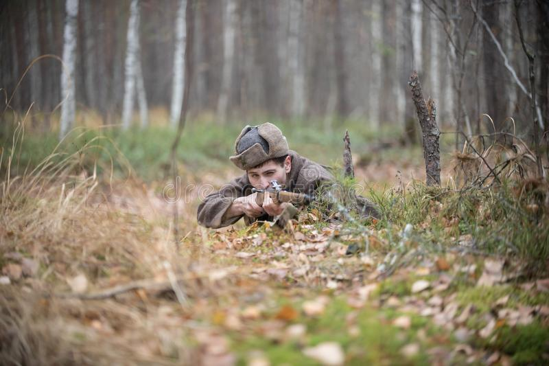 A soldier of World War II is lying in the forest and is going to shoot royalty free stock image