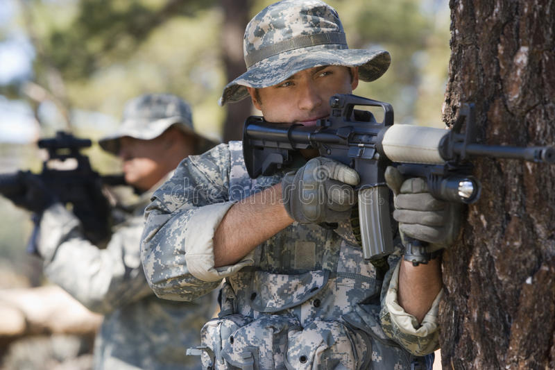 Soldiers Aiming Machine Guns. Soldiers in fatigues aiming with machine guns royalty free stock photos