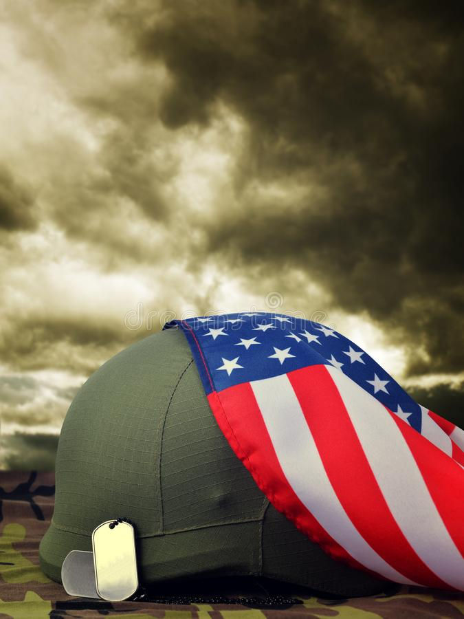 Soldiers badges,helmet and American flag on camouflage fabric. royalty free stock images