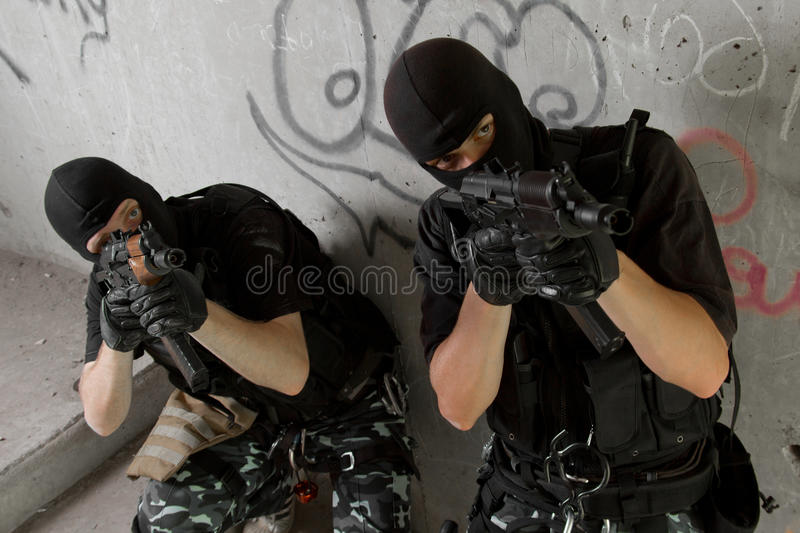 Soldiers in black masks moving upstairs stock images