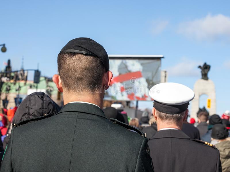 Soldiers from Canadian Army, two men, from Navy & ground forces, seen from behing, standing on ceremony for Remembrance day. OTTAWA, CANADA - NOVEMBER 11, 2018 royalty free stock photo