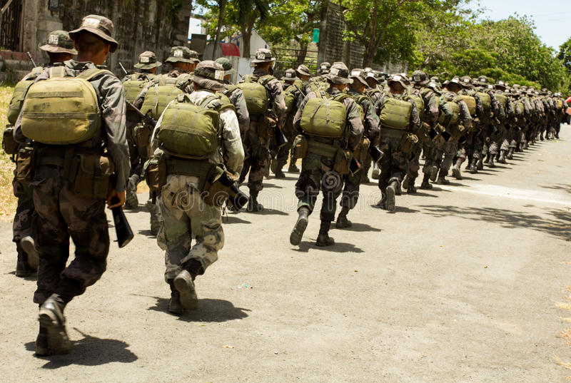 Soldiers in full combat gear running. FORT STO. DOMINGO,STA ROSA CITY,LAGUNA- April 10, 2013: Participants of COMMANDO training during a routine exercise held at royalty free stock images