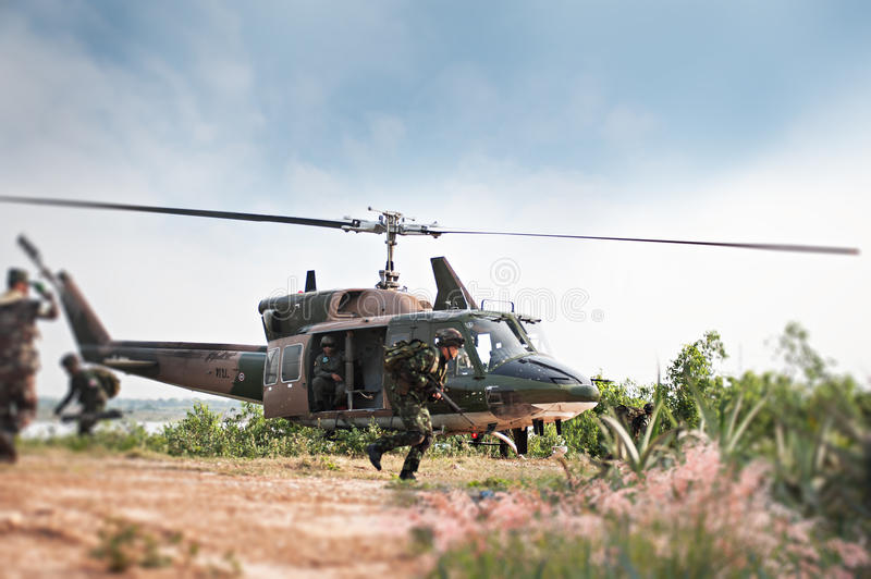 Soldiers holding gun and jumping from the helicopter stock image