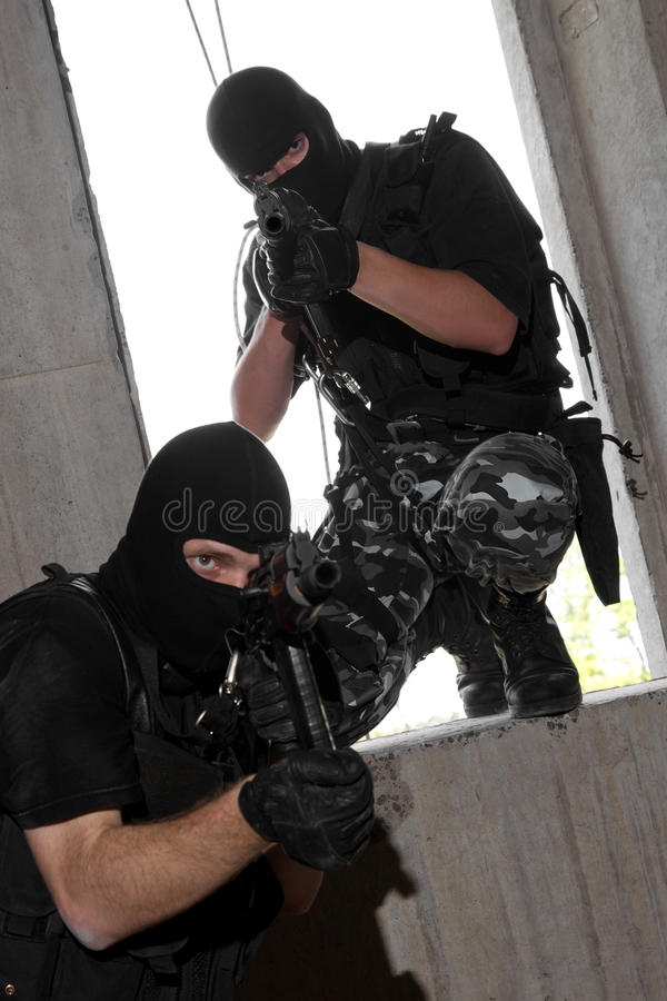 Soldiers in masks entering the window with rifles royalty free stock photography