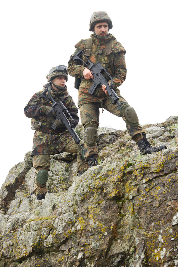 Soldiers moving on mountain with guns stock image