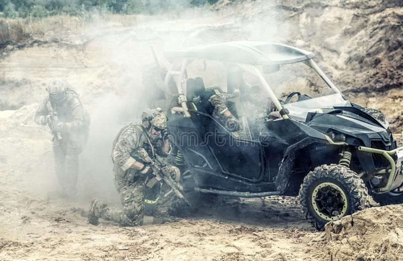 Soldiers on patrol vehicle in combat conditions. Mobile group of US commandos, special forces team on desert patrol vehicle fighting with enemy, covering royalty free stock photography