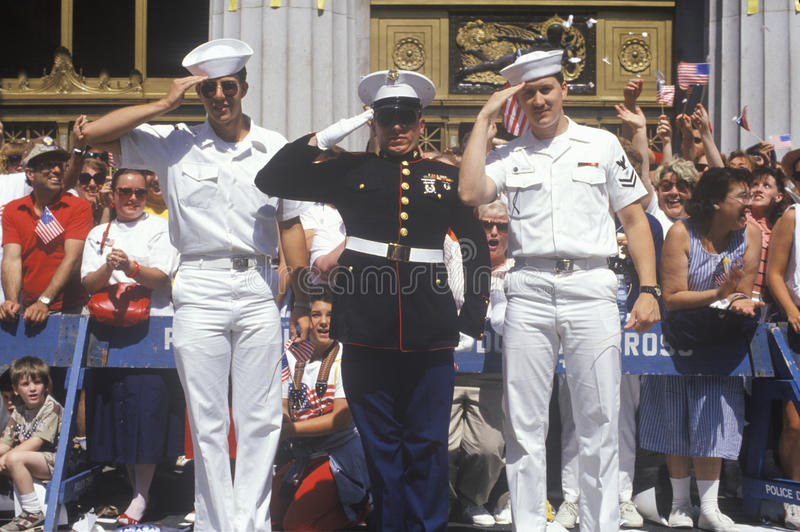 Soldiers Saluting. Two American Sailors and a United States Marine Saluting at Parade, America royalty free stock photography