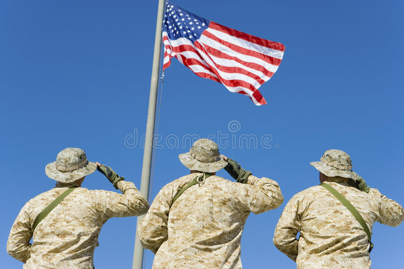 Soldiers Saluting An American Flag. Rear view of three soldiers saluting an American flag against blue sky royalty free stock photos
