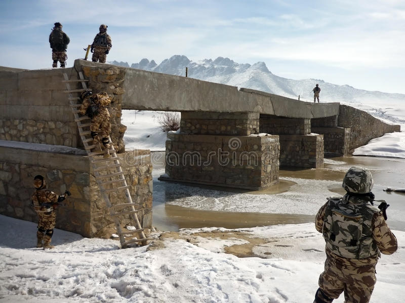 Soldiers searching a bridge in Afghanistan stock photos