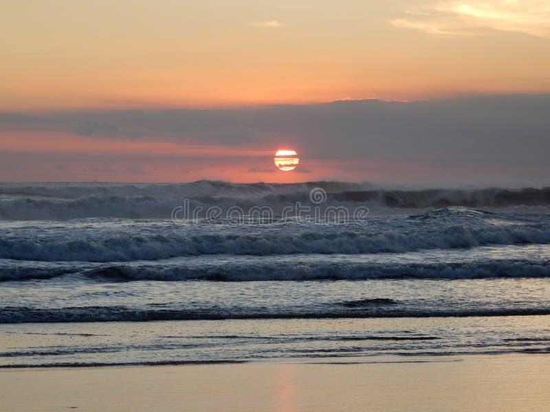 Soldiskett på solnedgången i molnen över det rasa havet royaltyfri fotografi