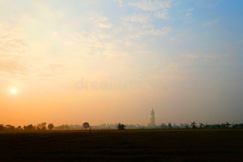 Sole di mattina che splende davanti al bello Buddha immagine stock