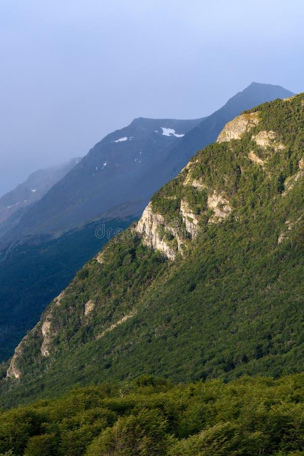Sole di sera che evidenzia pendio di collina roccioso in un fondo tempestoso, riserva naturale di Cerro Alarken, Ushuaia, Argenti fotografia stock