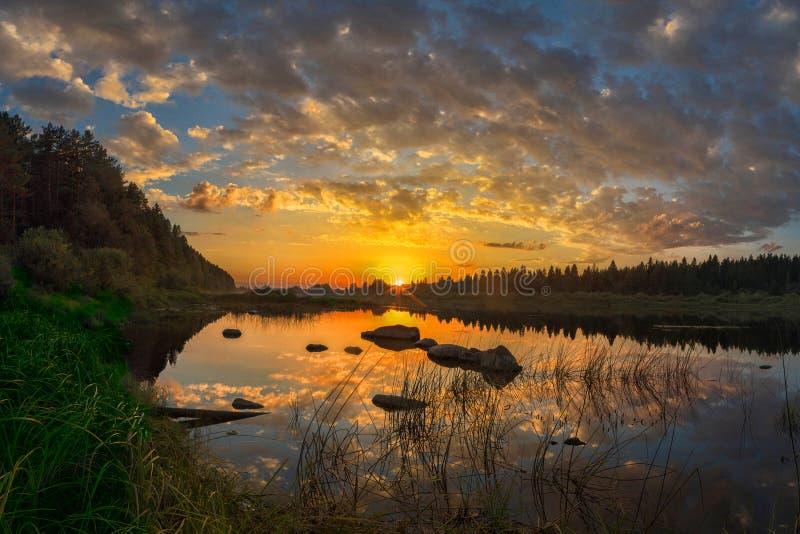 Sole di tramonto sopra il fiume con il cielo, con le belle nuvole e la riflessione sbalorditiva nell'acqua fotografia stock libera da diritti