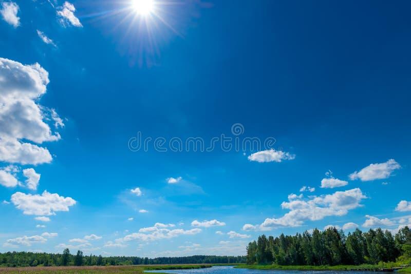 sole e cielo blu sopra un fiume pittoresco immagine stock