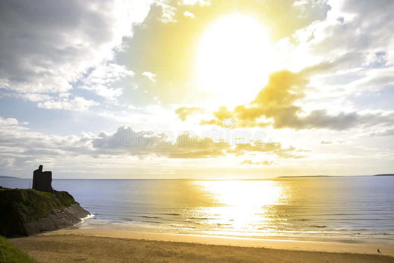 Sole giallo sopra la spiaggia ed il castello di Ballybunion fotografia stock
