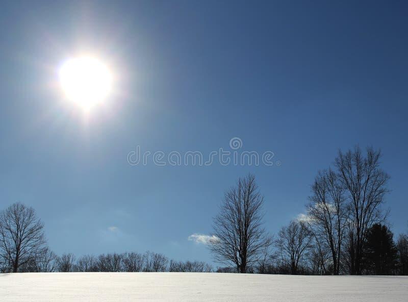 Sole luminoso su una collina innevata fotografie stock libere da diritti