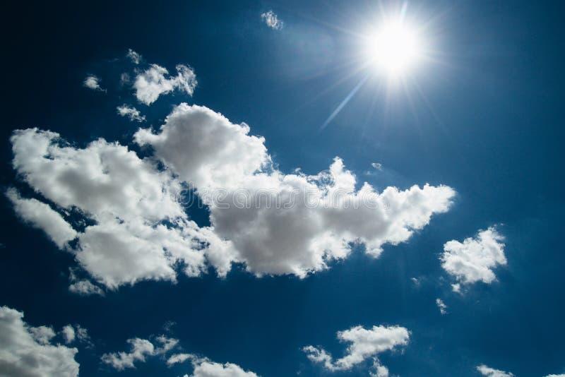 sole sui precedenti di un cielo blu con le nuvole bianche fotografia stock libera da diritti