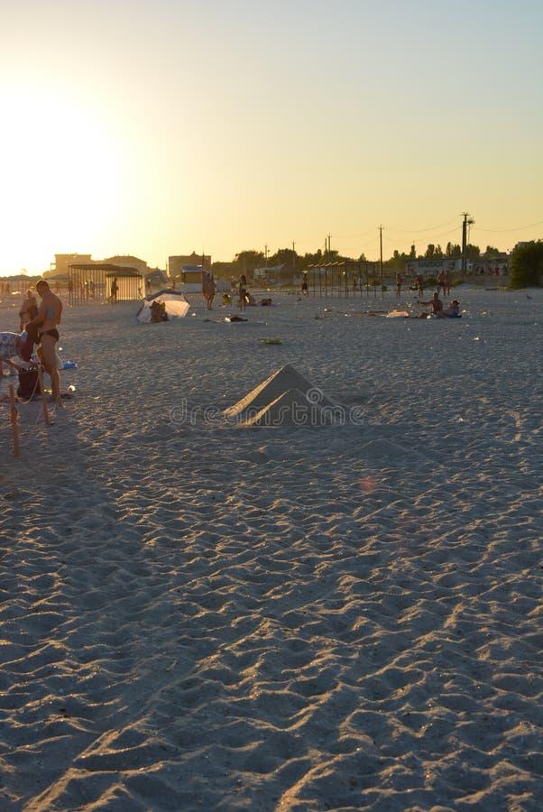 Soleado con puesta del sol del oro en la orilla del Mar Negro en un pío con dos pirámides en el fondo de la playa fotografía de archivo