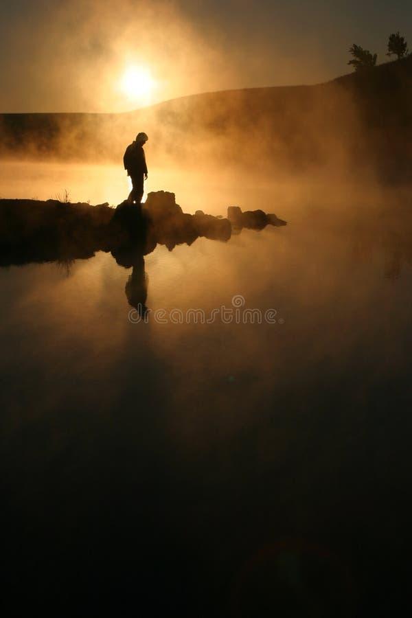 Soleil de matin et randonneur silhouetté par bordure de brouillard sur le lac calme images libres de droits