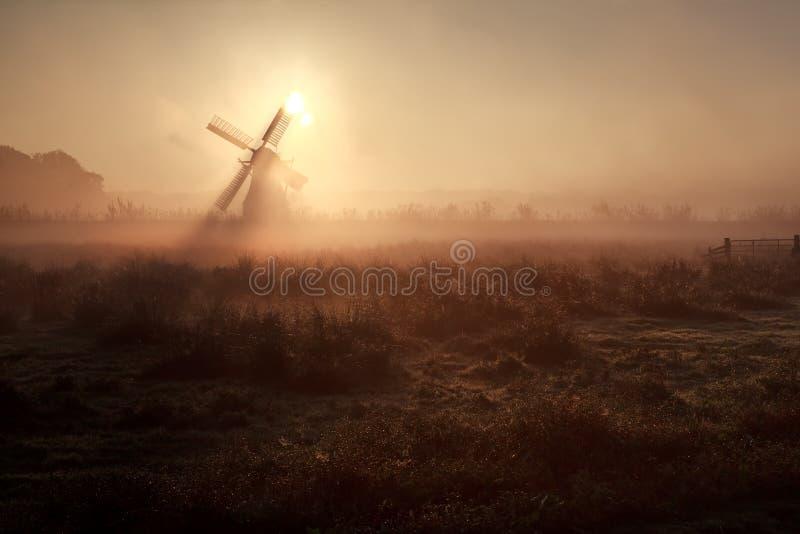Soleil derrière le moulin à vent dans le matin brumeux image libre de droits