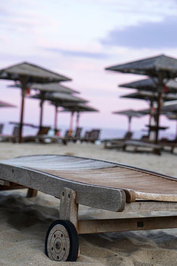 Soleil-lit en bois sur le sable de plage avec les parasols et le fond brouillé par ciel de coucher du soleil photographie stock