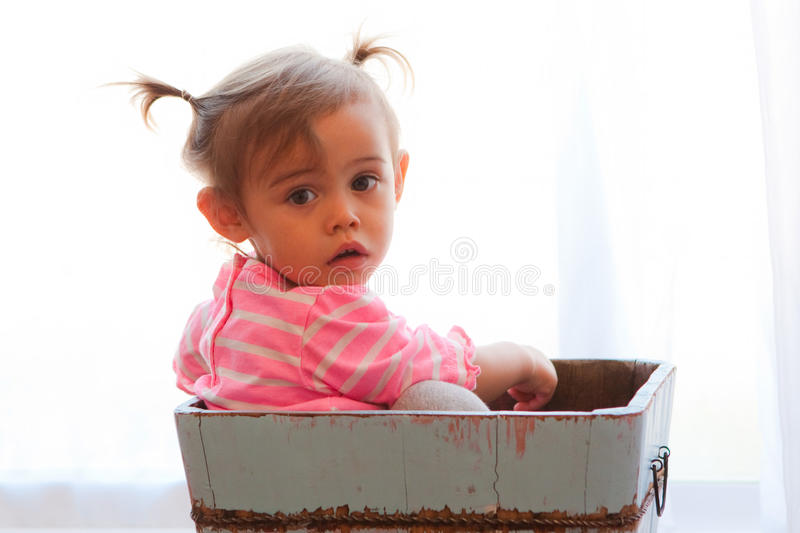 Solemn baby girl in wooden box. Cute but serious or solemn little baby girl sits in a rustic looking light blue wooden box. She is multicultural, asian and royalty free stock photography