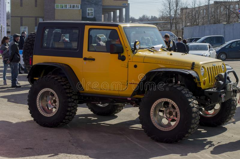 Solemn opening of the salon for the sale of automobiles. Jeep `Wrangler Rubicon` with large out-of-road wheels, Yellow. royalty free stock photos
