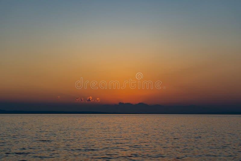 Solen är på väg att höja sig över molnen vid havshorisonten i Ioniska havet, vy från ön Zakynthos royaltyfria foton