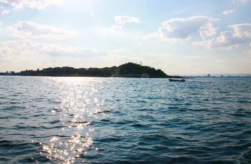 Solen blänker banan över havet Natur och stad p? horisonten Koppla av semestrar och sommarlivsstil bluen clouds skywhite royaltyfri fotografi