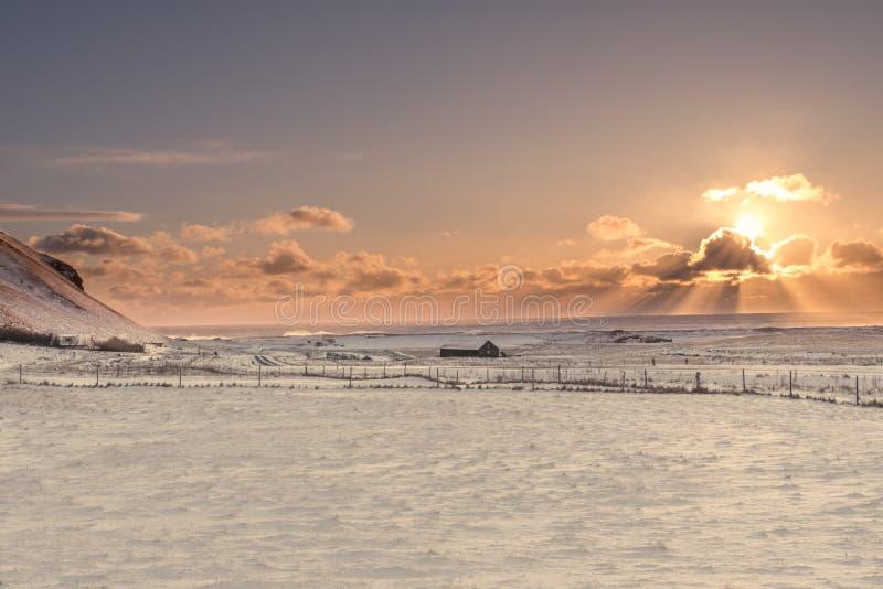 Solen brister bakifrån ett moln över det djupfrysta landskapet av arkivfoton