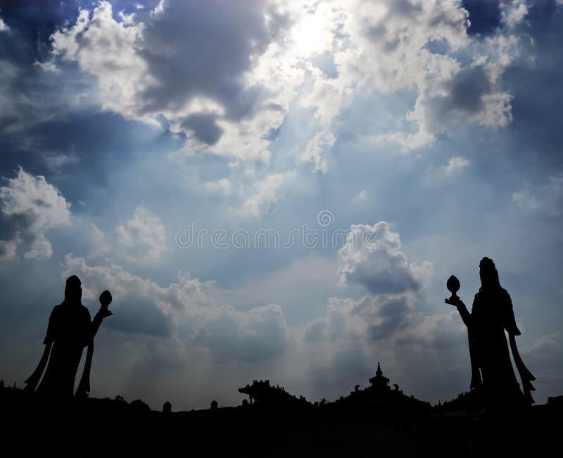 Solen gjuter moln för strålar bakifrån och gör en stark kontur av ett par av statyer och tempeltaken arkivbild