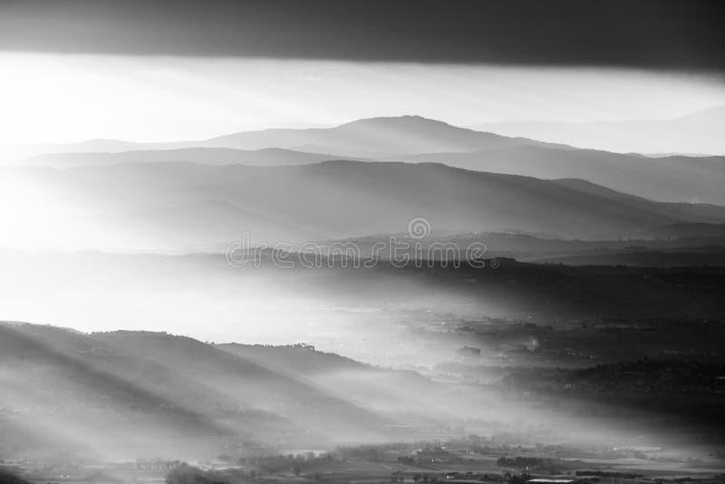 Solen rays över några berg och kullar på solnedgången fotografering för bildbyråer