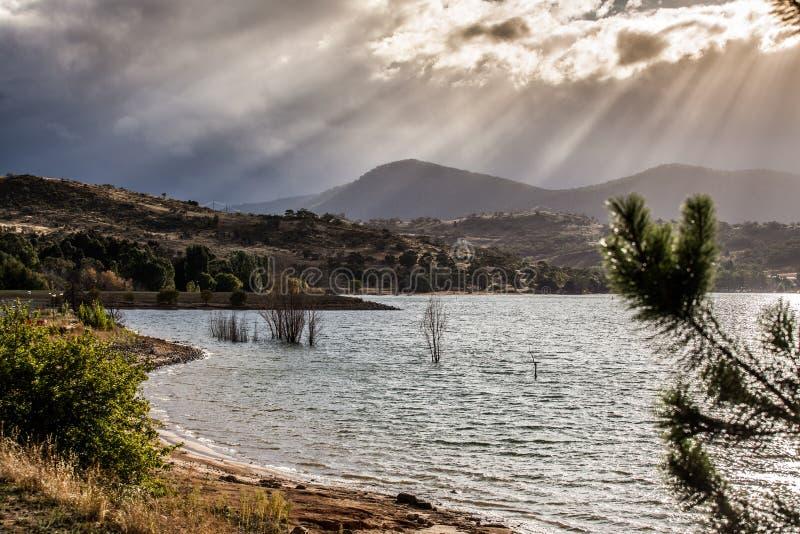 Solen Rays att skina till och med moln på kullarna av sjön Jindabyne, arkivbilder