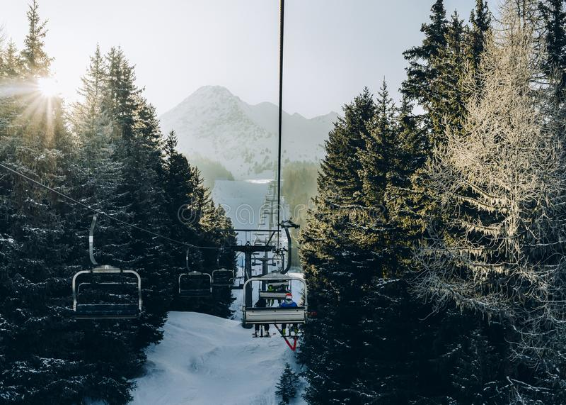 Solen sörjer igenom träd, som chairliftstigningen på italienare skidar område som täckas i snö royaltyfri bild