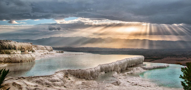Solen skiner bland molnen över Pamukkale Hierapolis arkivfoto