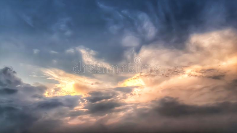 Solen skiner till och med molnen som svävar i himlen i aftonen royaltyfri fotografi