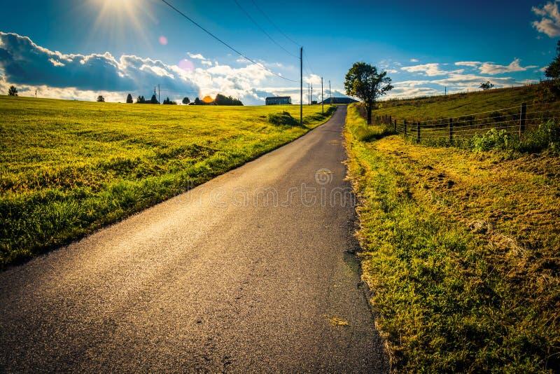 Solen som ställer in över en landsväg nära, korsar vägar, Pennsylvan royaltyfria foton