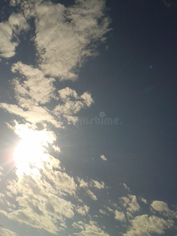 Solen som täckas av vit, fördunklar i himmel arkivfoton