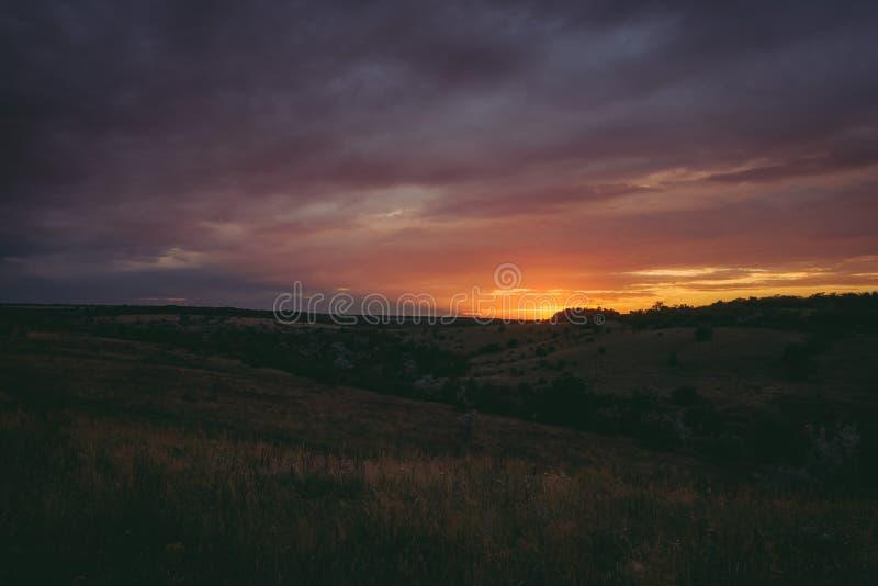 Solen ställer in över blasten av skogträd i moln Det panorama- fotoet av lilor, apelsinen och mörker fördunklar i himlen arkivfoto