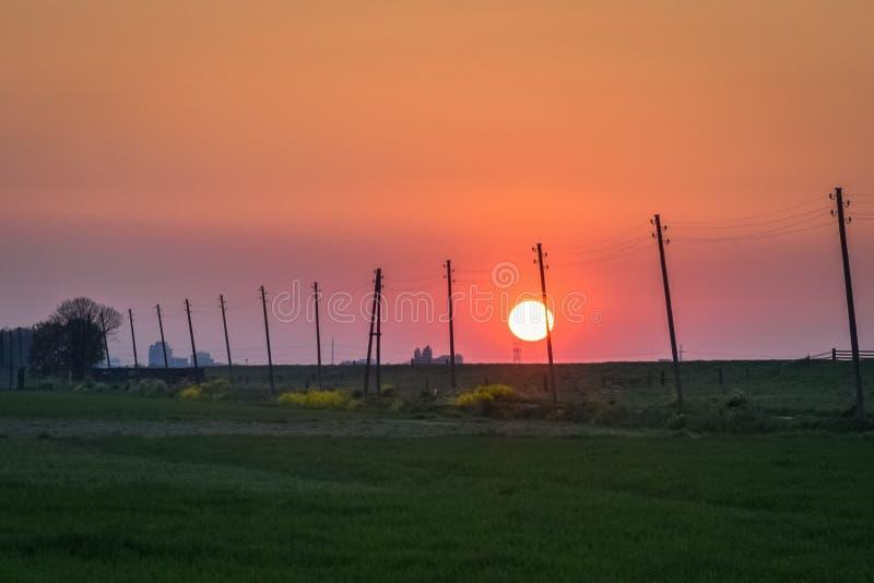 Solen ställer in över den holländska bygden, en väg med maktpoler försvinner i avståndet arkivbild