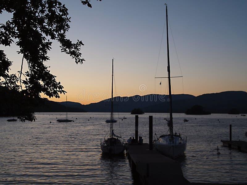Solen ställer in över sjön var fartygen är i hamnen och bakgrunden är berget royaltyfri bild