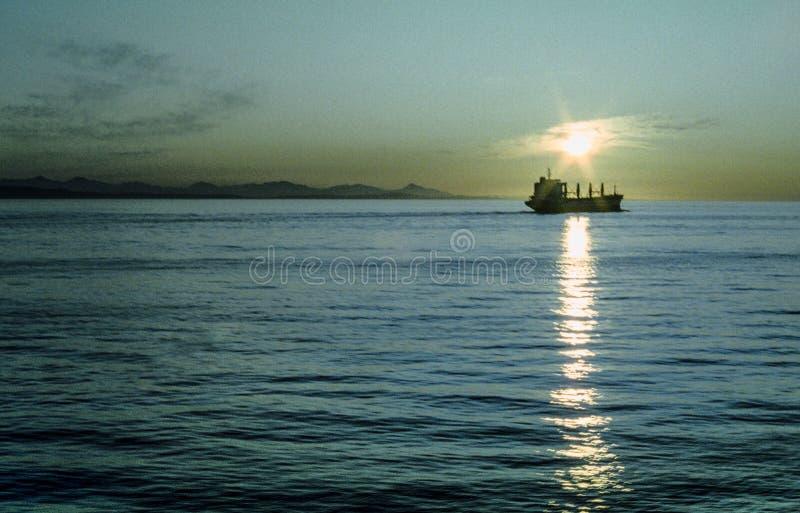 Solen ställer in på en skeppsegling i Stilla havet royaltyfri bild