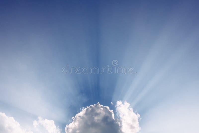 Solen strålar bakifrån ett moln royaltyfria bilder