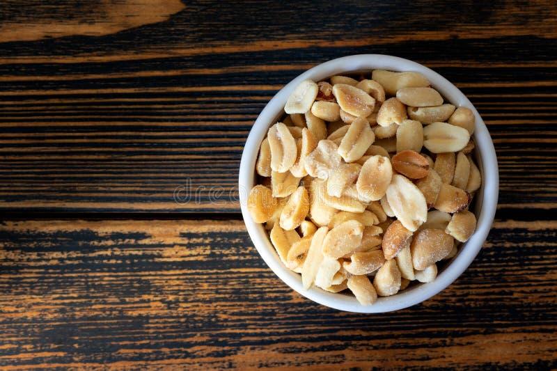Soleni arachidy w pucharze na drewnianym tle obrazy stock