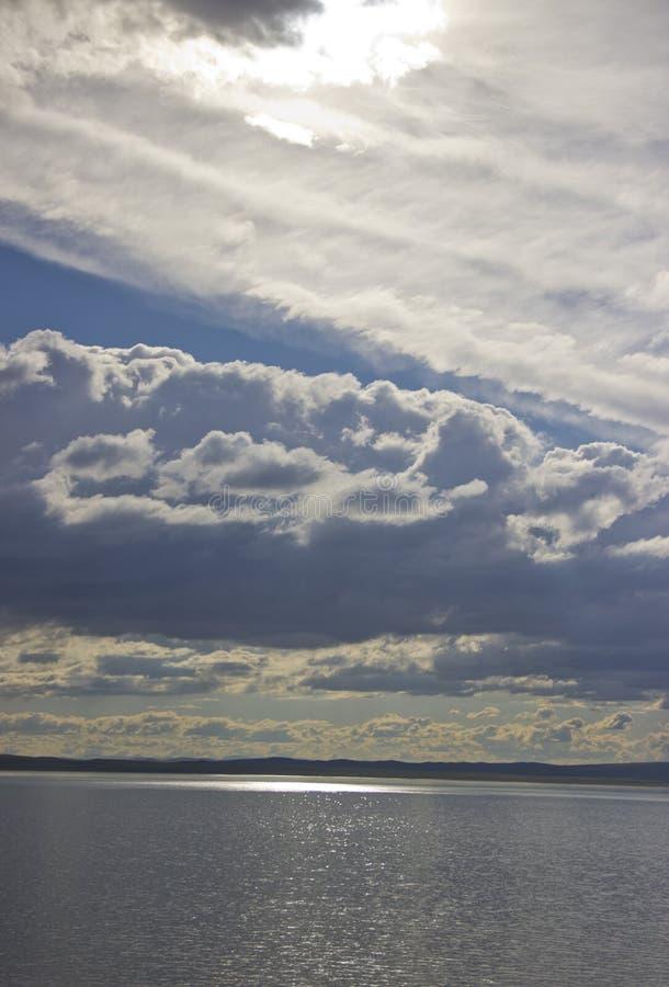 Solens strålar gör deras väg till och med molnen och exponerar sjön arkivbild
