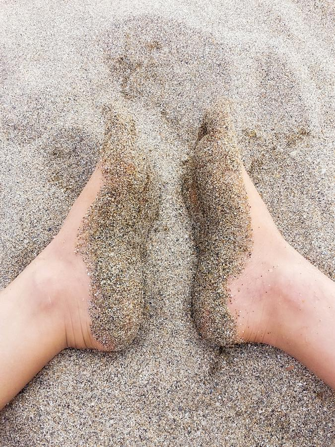 Soles of feet covered with dry sand. High angle view  of young caucasian women barefoot  on  beach .   Soles of feet covered  with dry sand.Summer holidays royalty free stock images