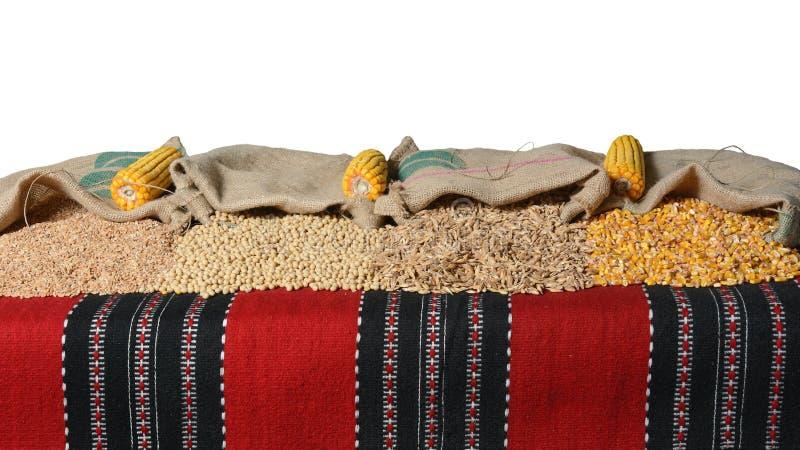 Soletrado, feijão de soja, grões do trigo e núcleos de milho em uns sacos da juta fotos de stock