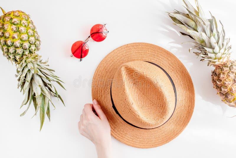 Solexponeringsglas, hatt, ananas i exotisk sommarfruktdesign på den vita modellen för bästa sikt för bakgrund royaltyfri fotografi