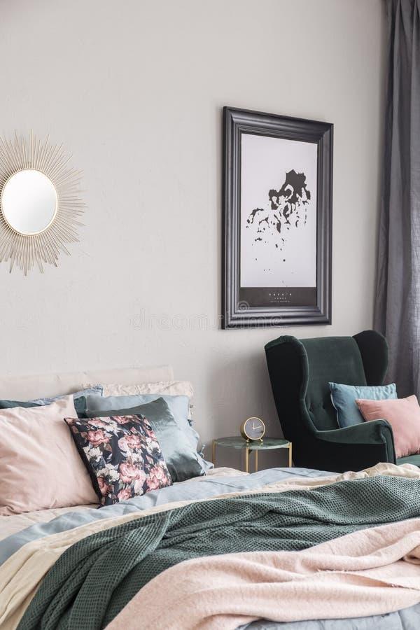 Solform som spegeln och översikt i svart ram på den gråa väggen av den trendiga sovruminre med konungformatsäng med hemtrevlig sä fotografering för bildbyråer
