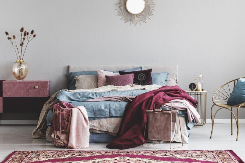 Solform som spegeln ovanför bekväm säng med hemtrevlig sängkläder fotografering för bildbyråer